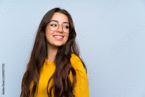 Teenager girl over isolated blue wall laughing