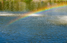 Rainbow Spray Fountain On The Background Of The River.