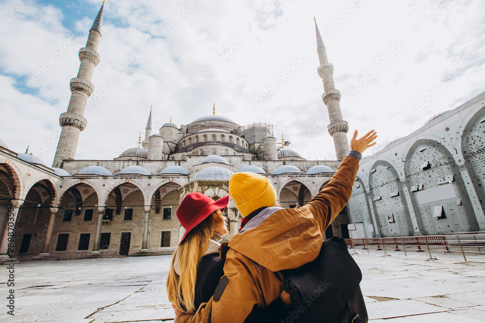Fototapety, obrazy: A young European couple walks in the courtyard of the Blue Mosque in Istanbul, Turkey. Traveler guy and girl in yellow hats walk in winter Istanbul. cloudy autumn day in Istanbul.