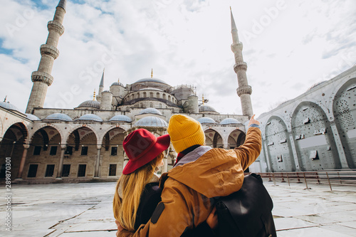 Photo  A young European couple walks in the courtyard of the Blue Mosque in Istanbul, Turkey