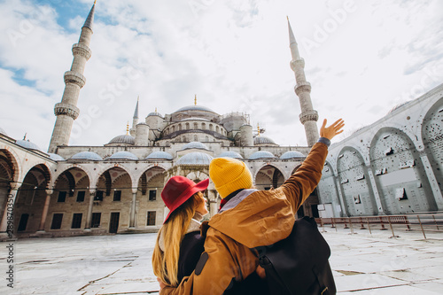 A young European couple walks in the courtyard of the Blue Mosque in Istanbul, Turkey Wallpaper Mural