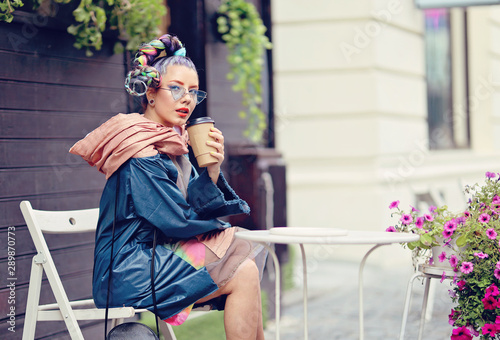obraz PCV Edgy girl with extravagant look sitting at a coffee shop table. Crazy appearance on the boulevard in old town - Avant-garde fashion concept