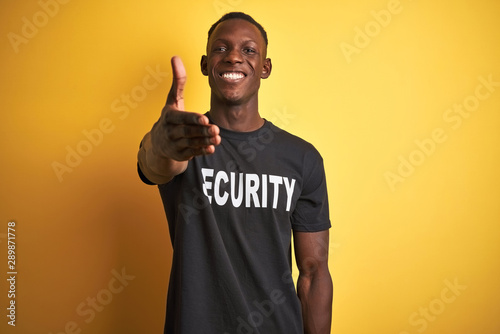Fototapeta African american safeguard man wearing security uniform over isolated yellow background smiling friendly offering handshake as greeting and welcoming. Successful business. obraz na płótnie
