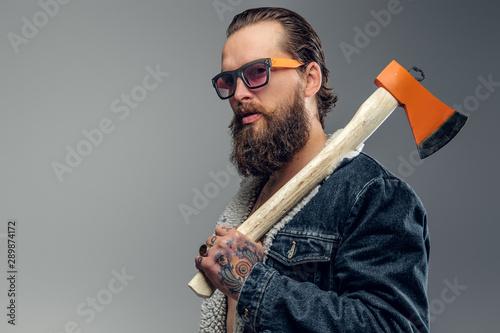 Fényképezés  Brutal bearded man in sunglasses and denim jacket is holding axe.