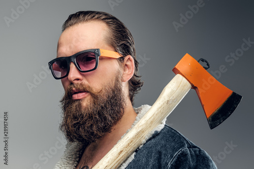 Pinturas sobre lienzo  Brutal bearded man in sunglasses and denim jacket is holding axe.