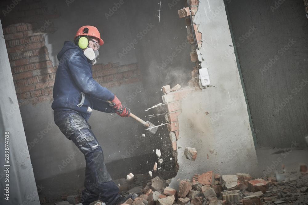 Fototapeta demolition work and rearrangement. worker with sledgehammer destroying wall