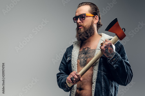 Brutal bearded man in sunglasses and denim jacket is holding axe. Fototapet