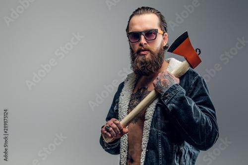 Brutal bearded man in sunglasses and denim jacket is holding axe. Tapéta, Fotótapéta
