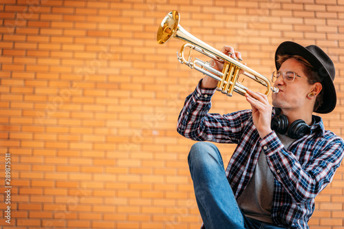 handsome man with eye glasses and hat poses with trumpet - 289875511