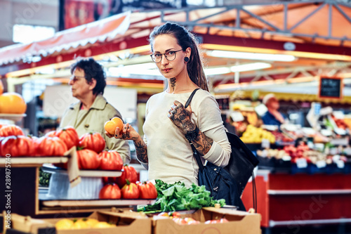 Pensive tattoed girl is carefully choosing tomatoes on a local farmer's market Canvas Print