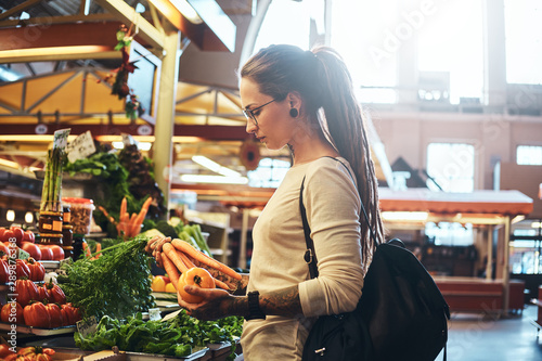 Beautiful pensive girl in glasses is buying fresh carrots at local farmer's market Canvas Print