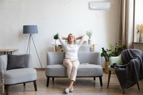 Relaxed older woman sitting on couch in air conditioner room Canvas Print