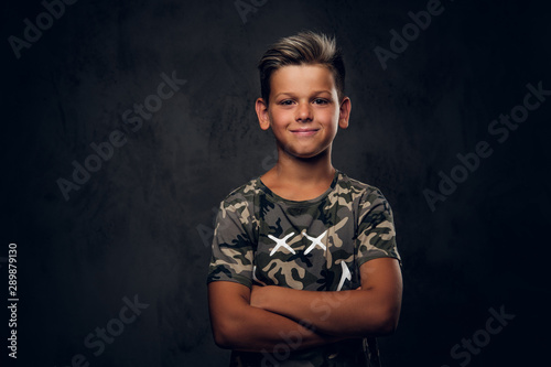 mata magnetyczna Little charming boy with nice hairstyle is posing over dark background at photo studio.