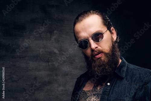 Canvastavla Portrait of brutal bearded man in sunglasses at dark photo studio