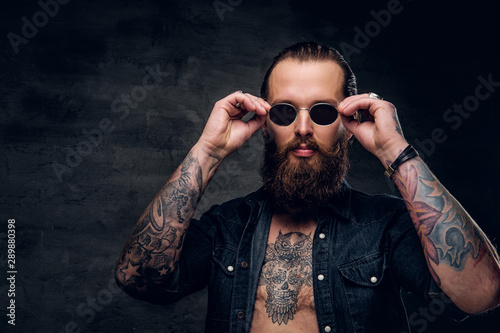 Fotografiet  Portrait of brutal bearded man with tattooes at dark photo studio