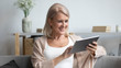 canvas print picture Smiling mature woman using computer tablet apps, having fun