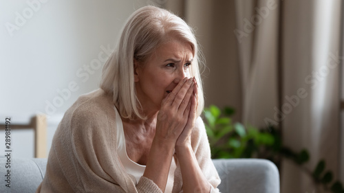 Upset mature woman crying, sitting alone, feeling lonely and unwell Tableau sur Toile