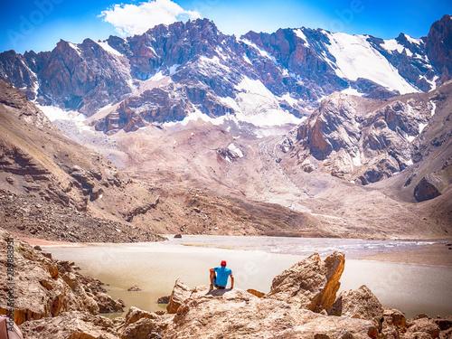 In de dag Zalm Hiker near Lake Moutniy on rocky mountain background. Fann Mountains, Tajikistan, Central Asia