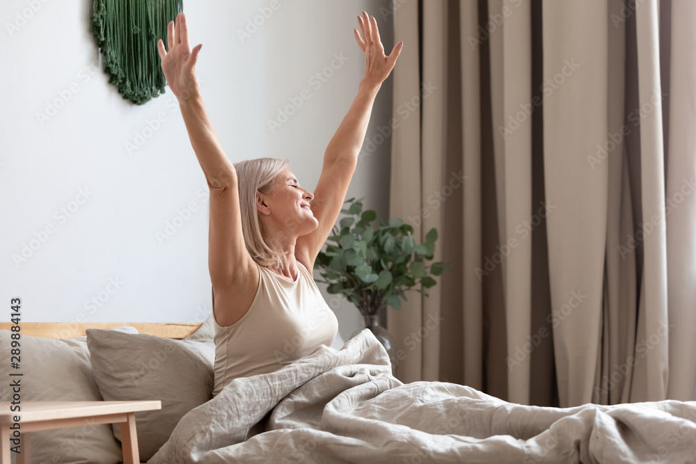 Fototapety, obrazy: Happy older woman sitting in bed, stretching hands after awakening