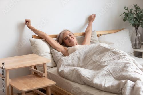 Obraz Beautiful mature woman stretching hands in bed after awakening - fototapety do salonu