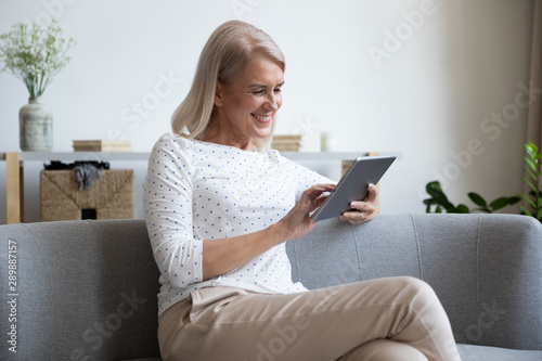 Smiling mature woman using computer tablet at home