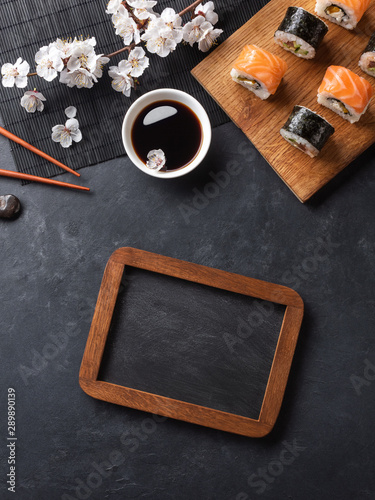 Fototapeta Set of sushi and maki rolls with branch of white flowers and chalk board on stone table obraz