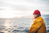 Alone man traveling on ship and looking at sunset sea and foggy mountain on skyline. Hipster traveler wearing yellow raincoat and red hat enjoying beautiful ocean after storm