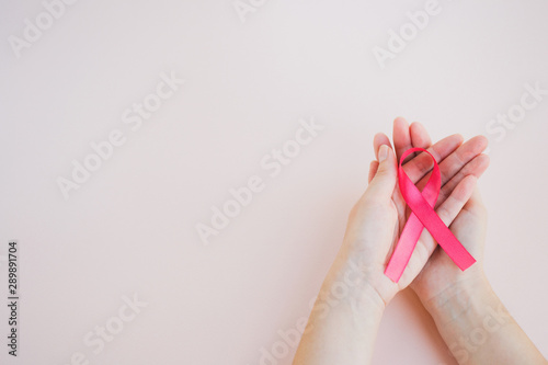 Womans hands hold pink breast cancer awareness ribbon on a light background. Medicine and healthcare concept, women's health. Top view, copy space #289891704