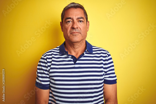 Fototapeta Handsome middle age man wearing striped polo standing over isolated yellow background with serious expression on face. Simple and natural looking at the camera. obraz na płótnie