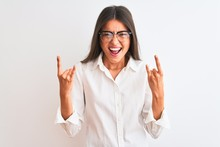 Young Beautiful Businesswoman Wearing Glasses Standing Over Isolated White Background Shouting With Crazy Expression Doing Rock Symbol With Hands Up. Music Star. Heavy Music Concept.