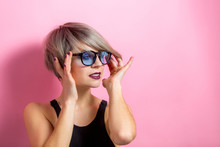 Fashion Beautiful Young Woman With Short Hair And Sunglasses Over Pink Background