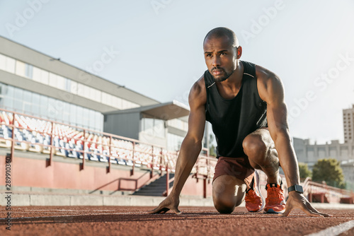 Photo Low angle view of young man athlete in starting position for running on sports t