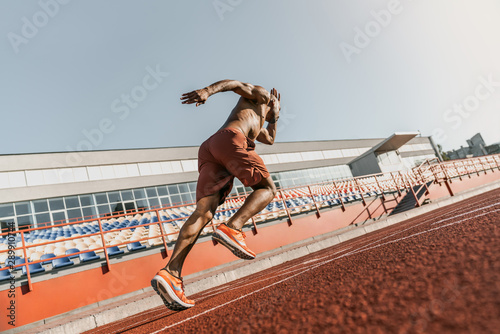 Rear view of an athlete starting his sprint on an all-weather running track Wallpaper Mural