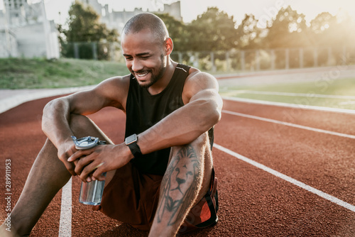 Fototapeta  Cheerful young sporty man sitting on stadium running track with bottle of water