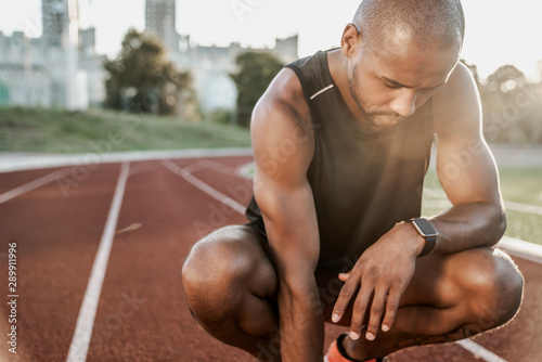 Valokuva  Portrait of tired african male athlete finished workout and resting while sittin