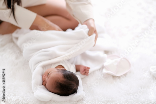 Obraz Newborn baby was swaddling with white cloth by her mother and the activity is on bed. - fototapety do salonu