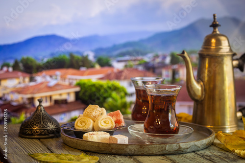 Photo Stands Tea Glass Cup of turkish tea served in traditional style with summer outdore view