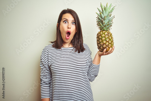Obraz na plátně  Young beautiful woman holding tropical fruit pineapple over isolated background