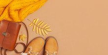 Brown Leather Women Bag, Orange Knitted Sweater, Warm Boots, Golden Autumn Leaf On Brown Background Top View Flat Lay. Fashionable Women's Accessories. Autumn Fashion Concept. Stylish Lady Clothes