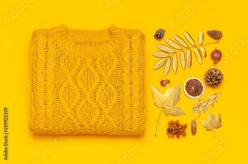 Autumn flat lay composition. Orange yellow knitted woolen female sweater and golden leaves on yellow background top view. Fashionable women's fall accessories. Cozy Knit Jumper Stylish Lady Clothes