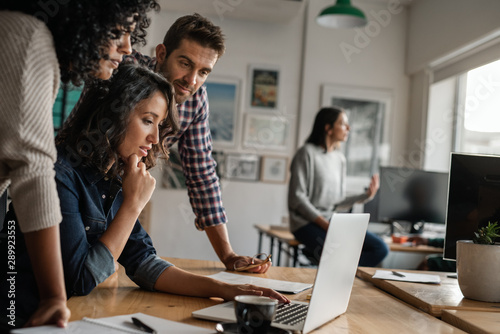 Three young designers working on a laptop in an office