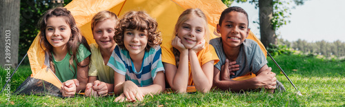 Obraz panoramic shot of happy multicultural kids smiling while lying near camp - fototapety do salonu
