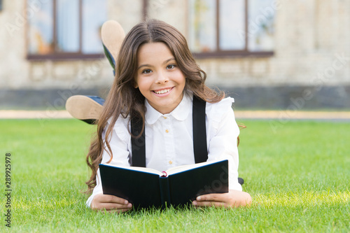 Basic education. Extracurricular reading. Cute small child reading book outdoors. Adorable little girl learn reading. Schoolgirl school uniform laying on lawn with favorite book. Studying concept