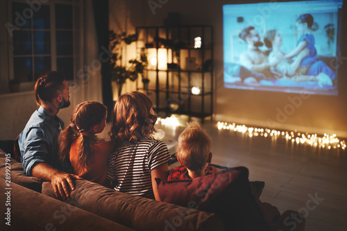 Fotomural family mother father and children watching projector, TV, movies with popcorn in   evening   at home