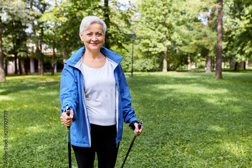 Fit happy gray haired mature female in sportswear enjoying health-promoting phys Wallpaper Mural