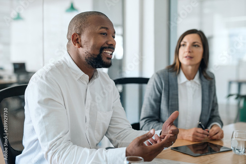 Carta da parati  Smiling African American businessman talking with coworkers during a meeting