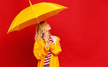 Young Happy Emotional Cheerful Girl Laughing  With Yellow Umbrella   On Colored Red Background.
