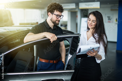 Photo Professional gorgeous saleswoman consult man at car dealership in formal wear