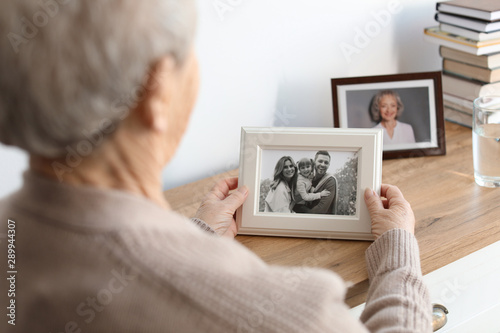Leinwand Poster Elderly woman with framed family portrait at home