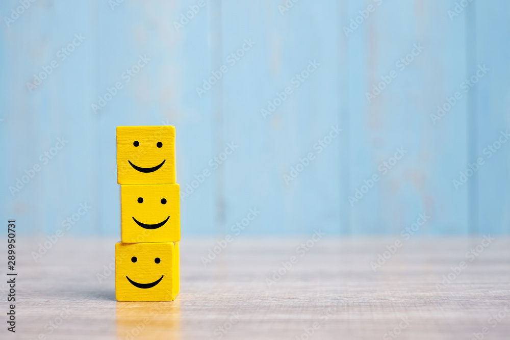 Fototapeta smile face on yellow wood cube. Service rating, ranking, customer review, satisfaction and emotion concept.